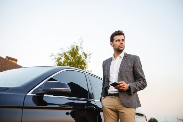 Confident young businessman in suit standing at his car